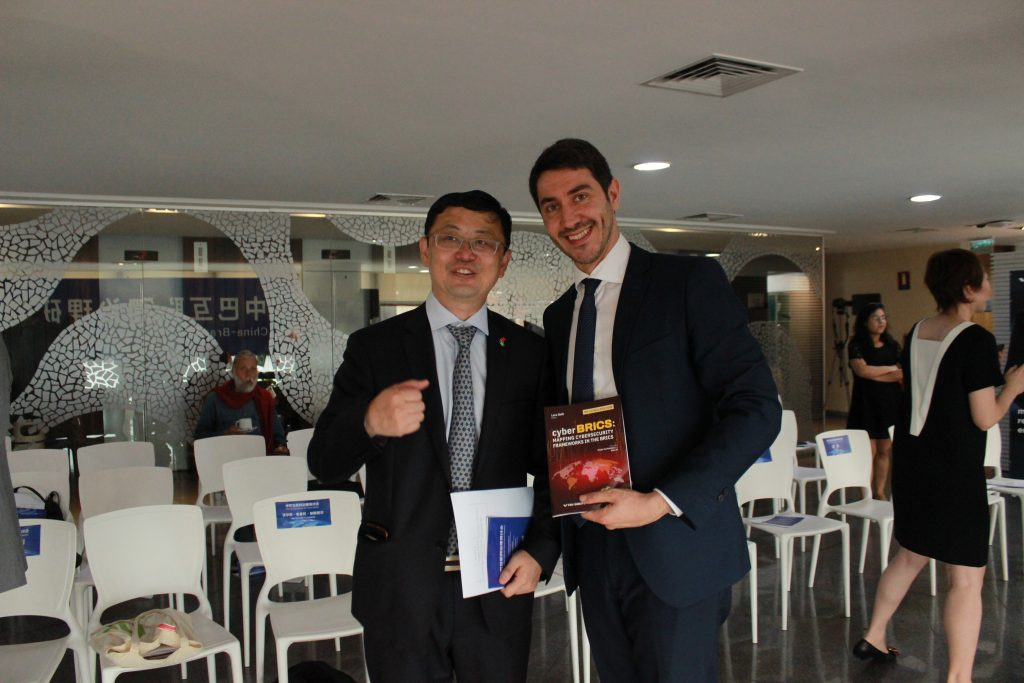 CyberBRICS' director, Luca Belli, gives a copy of the book to a chinese representative